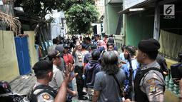 Kerumunan warga menyaksikan polisi menggeledah kediaman orang tua terduga teroris di Jalan Belibis V, Semper Barat, Cilincing, Jakarta, Senin (23/9/2019). Selain rumah tersangka, polisi juga menggeledah kediaman orang tua terduga teroris yang tidak jauh dari TKP. (merdeka.com/Iqbal S. Nugroho)