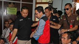 Terdakwa kasus penghancuran barang bukti dugaan pengaturan skor Joko Driyono (tengah) dikawal petugas saat akan menjalani sidang di PN Jakarta Selatan, Jakarta, Kamis (4/7/2019). Jaksa menilai terdakwa terbukti melanggar Pasal 235 jo Pasal 231 dan Pasal 55 ayat 1 ke-1 KUHP. (Liputan6.com/Herman Zakh