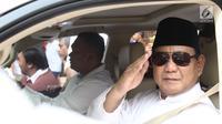 Bakal Calon Presiden, Prabowo Subianto melakukan gerakan hormat dari dalam mobilnya  saat perjalanan menuju Gedung KPU, Jakarta, Jumat (10/8). Ketua Umum Gerindra itu berangkat ke KPU untuk mendaftarkan diri sebagai capres. (Liputan6.com/Herman Zakharia)