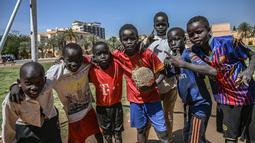 Sejumlah anak Sudan berpose sebelum bermain sepak bola di ibu kota Khartoum (23/4). Negara ini berbatasan dengan Mesir di utara, Laut Merah di timur laut, Kongo dan Afrika Tengah di barat daya, Chad di barat, dan Libya di barat laut. (AFP Photo/Ozan Kose)