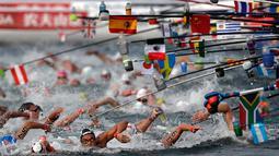 Perenang meraih botol minuman saat berlaga dalam lomba renang air terbuka nomor 10 km putra di Kejuaraan Renang Dunia di Yeosu, Korea Selatan, Selasa (16/7/2019). (AP Photo/Mark Schiefelbein)