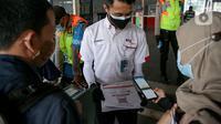 Petugas membantu calon penumpang memindai kode batang (QR Code) melalui aplikasi PeduliLindungi sebelum menaiki KRL di Stasiun Manggarai, Jakarta, Selasa (7/9/2021). PT KAI Commuter melakukan uji coba penggunaan aplikasi PeduliLindungi bagi pengguna KRL di 11 stasiun. (Liputan6.com/Faizal Fanani)