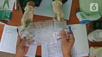 Petugas medis memberikan kantung udara kepada warga saat peluncuran Layanan GeNose C-19 di Kantor Dompet Dhuafa, Jakarta, Selasa (9/3/2021).  Dompet Dhuafa meluncurkan layanan pemeriksaan tes Covid-19 dengan menggunakan metode GeNose C-19. (Liputan6.com/Herman Zakharia)