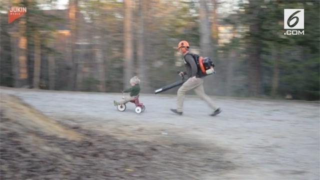 Seorang ayah yang membantu anaknya bermain sepeda roda tiga dengan blower daun.