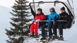Presiden Rusia Vladimir Putin (kiri) dan Presiden Belarusia Alexander Lukashenko (kanan) menaiki lift ski saat akan bermain ski di Krasnaya Polyana dekat resor Laut Hitam Sochi, Rusia, Rabu (13/2). (Sergei Chirikov/Pool Photo via AP)