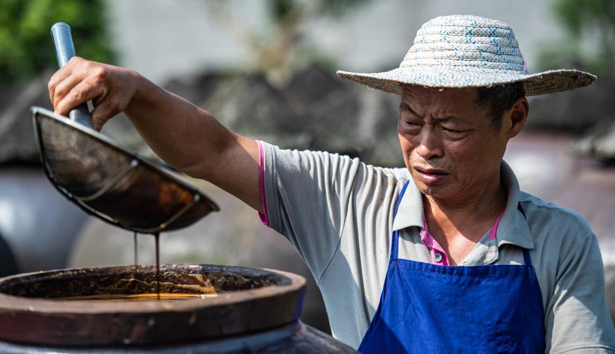 Seorang pekerja memeriksa kualitas cuka di Chishui, Provinsi Guizhou, China barat daya (26/6/2020). Chishui terkenal dengan cuka mataharinya, yang masih mempertahankan proses pembuatan secara tradisional. (Xinhua/Tao Liang)