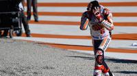 Pembalap Spanyol Repsol Honda, Marc Marquez meluapkan kegembiraannya sambil memegang kepala setelah memenangkan balapan seri ke 18 MotoGP Grand Prix Valencia di Sirkuit Ricardo Tormo, Valencia (12/11). (AFP PHOTO / Jose Jordan)
