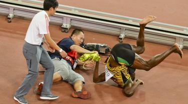Pelari Jamaika, Usain Bolt terjungkal usai tertabrak kameramen yang mengendarai skuter saat dirinya melakukan selebrasi kemenangan meraih medali emas di nomor 200 meter pada Kejuaran Dunia Atletik di Beijing, Kamis (27/8). (REUTERS/Stringer CHINA OUT)