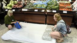 Pelanggan menyiapkan kasur di toko kelontong  yang mengizinkan untuk menginap di Helsinki, 4 Agustus 2018. Finlandia tengah dilanda gelombang panas yang mengakibatkan warganya terpaksa menginap di dalam ruangan ber-AC. (Heikki Saukkomaa/Lehtikuva /AFP)