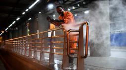 Pekerja membersihkan stasiun bus sebagai tindakan pencegahan dalam menghadapi pandemi global virus corona COVID-19 di Cali, Kolombia (14/3/2020). Kolombia mengambil tindakan luar biasa seperti melarang turunnya kapal pesiar dan mengadakan acara publik dengan lebih dari 500 peserta. (AFP/Luis Robayo)