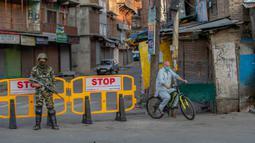 Pria Kashmir melintasi barikade yang digunakan untuk memblokir jalan di Srinagar, Kashmir yang dikuasai India, Rabu (5/8/2020). Tentara India memperketat keamanan di Kashmir dalam upaya menahan serangan dalam peringatan setahun pelepasan status otonomi khusus wilayah tersebut. (AP Photo/ Dar Yasin)