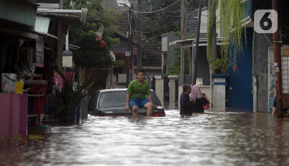 Warga duduk di atas mobil saat banjir merendam jalan dan rumah di RT 003/05, Pejaten, Jakarta, Sabtu ( 20/2/2021). Curah hujan yang tinggi sejak malam hingga dini hari mengakibatkan sejumlah kawasan terendam banjir. (merdeka.com/Imam Buhori)