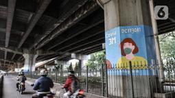 Pengendara motor melintasi mural bertema protokol kesehatan Covid-19 yang menghiasi tiang pancang jalan tol di Jalan Ahmad Yani, Jakarta, Minggu (13/12/2020). Warna-warni mural ini dibuat oleh seniman dari berbagai daerah. (merdeka.com/Iqbal S. Nugroho)
