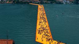 """Ribuan wisatawan berjalan di atas instalasi """"The Floating Piers"""" di Danau Iseo, Italia utara, (24/6). Seni instalasi sepanjang 1,9 mil ini terbuat dari 200.000 batu apung yang ditutupi kain oranye. (REUTERS/Stefano Rellandini)"""