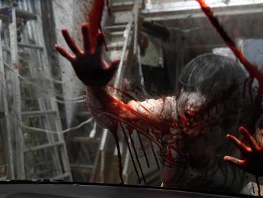 Pemeran zombie tampil dengan darah palsu yang disiramkan ke kaca kendaraan saat demonstrasi pertunjukan rumah hantu drive-in di Tokyo, Jepang, Selasa (18/8/2020). Rumah hantu drive-in ini diadakan di tengah pandemi COVID-19. (AP Photo/Eugene Hoshiko)