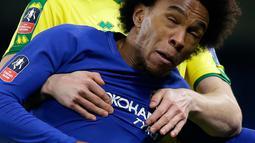 Pemain Chelsea Willian melompat untuk merebut bola dari pemain Norwich City Timm Klose pada laga ulangan babak ketiga Piala FA di Stadion Stamford Bridge, Rabu (17/1). Chelsea melaju ke babak keempat Piala FA lewat kemenangan dramatis. (AP/Alastair Grant)