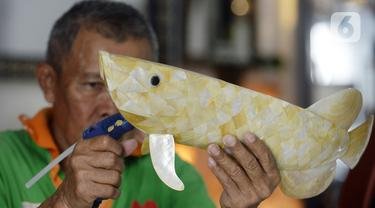 Perajin menyelesaikan pembuatan kerajinan tangan dari kulit kerang di Pamulang 2, Tangerang Selatan, Banten, Senin (20/7/2020). Aneka kerajinan tangan dengan motif bunga hingga ikan tersebut diolah dari limbah kulit kerang. (merdeka.com/Dwi Narwoko)