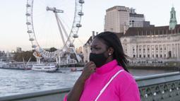 Seorang wanita yang mengenakan masker berjalan di Jembatan Westminster dengan latar pemandangan London Eye di London, Inggris (31/10/2020). Kasus baru COVID-19 di Inggris mencapai 21.915, menambah total kasus coronavirus di negara itu menjadi 1.011.660. (Xinhua/Han Yan)
