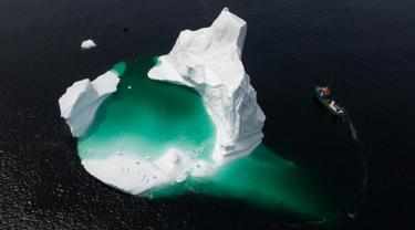 Kapal Kapten Edward Kean melewati gunung es terapung di Teluk Bonavista, Newfoundland, Kanada, 29 Juni 2019. Banyaknya gunung es terapung menjadikan Newfoundland destinasi wisata baru di Kanada. (Johannes Eisele/AFP)