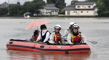 Warga dievakuasi menggunakan perahu karet saat banjir merendam daerah Asakura di prefektur Fukuoka, Kamis (6/7). Hujan lebat yang disebabkan angin topan di selatan Jepang telah memaksa evakuasi hampir 400.000 orang. (Sadayuki Goto/Kyodo News via AP)