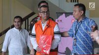 Mantan Dirut PT Garuda Indonesia Emirsyah Satar (tengah) menutupi borgol di tangannya dengan map merah saat akan menjalani pemeriksaan di Gedung KPK, Jakarta, Jumat (16/8/2019). Satar diperiksa sebagai tersangka terkait kasus dugaan suap pengadaan mesin Rolls-Royce PLC. (merdeka.com/Dwi Narwoko)