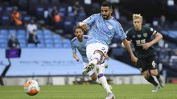 Pemain Manchester City, Riyad Mahrez, mencetak gol ke gawang Burnley pada laga Premier League di Stadion Etihad, Senin (22/6/2020). Manchester City menang 5-0 atas Burnley. (AP/Shaun Botterill)