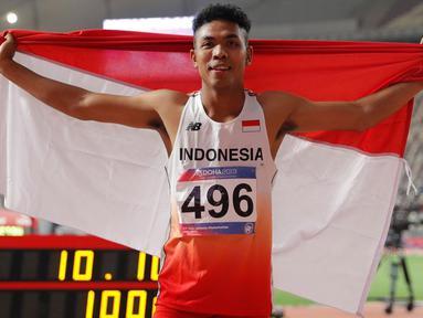 Sprinter Indonesia, Lalu Muhammad Zohri mengibarkan bendera Merah Putih seusai mengikuti kategori 100 meter dalam semifinal Kejuaraan Atletik Asia di Doha, Qatar, Senin (22/4/2019). Lalu Muhammad Zohri sukses menggondol medali perak setelah membukukan catatan waktu 10,13 detik. (AP/Vincent Thian)