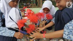 Murid-murid membuat kerajinan tangan dari limbah plastik dan kardus di SMPN 20 Tangsel, Kamis (10/10/2019). Kegiatan dalam program Gerakan Sekolah Menyenangkan ini  untuk menggugah kesadaran sejak dini kepedulian pengelolaan sampah yang dapat diolah dengan kreatifitas. (merdeka.com/Arie Basuki)