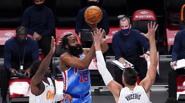 Pebasket Brooklyn Nets, James Harden, berusaha melewati pebasket Orlando Magic, Nikola Vucevic dan Dwayne Bacon pada laga NBA, Sabtu (16/1/2021). Nets menang dengan skor 122-115. (AP Photo/Mary Altaffer)
