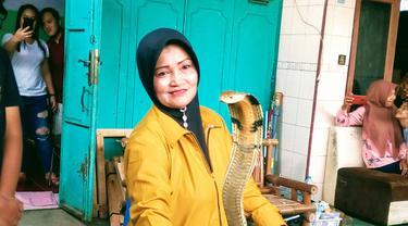 Iin Ayu (55) bersama satu di antara ular King Kobra peliharaannya di rumahnya di Kelurahan Karangpucung, Kecamatan Purwokerto Selatan, Kabupaten Banyumas, Selasa (17/12/2019). (Liputan6.com/Rudal Afgani Dirgantara)