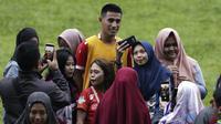 Pemain Arema FC, Hanif Sjahbandi, foto bersama dengan fans usai sesi latihan di Stadion Gajayana, Malang, Kamis (11/4). Setelah sesi latihan, pemain Arema FC melayani permintaan fans untuk foto bersama. (Bola.com/Yoppy Renato)