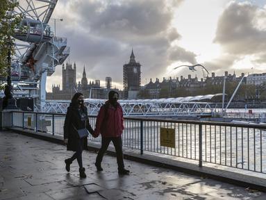 Sejumlah warga yang mengenakan masker berjalan di tepi Sungai Thames di London, Inggris (31/10/2020). Kasus baru COVID-19 di Inggris mencapai 21.915, menambah total kasus coronavirus di negara itu menjadi 1.011.660. (Xinhua/Han Yan)