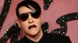 Pose Marilyn Manson saat menghidiri di Fashion Awards 2016 di London, Inggris (5/12). Mantan pacar Evan Rachel Wood tersebut tampil Fashionable dengan Jas dan kacamata hitam dengan gigi dan cincin ditangannya. (REUTERS/Neil Balai)