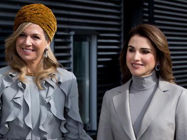 Ratu Belanda Maxima (kiri) berpose untuk foto bersama Ratu Yordania Rania saat berkunjung ke sekolah Mondriaan ROC di Den Haag, Belanda (21/3). Kedua ratu itu tampil senada menggunakan busana berwarna abu-abu. (AP Photo / Peter Dejong)