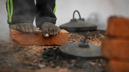 Pekerja migran India berdiri di atas batu bata dan menghangatkan dirinya di atas tungku di sebuah pabrik batu bata di pinggiran Kathmandu. Ribuan pekerja migran India datang ke Nepal untuk bekerja di pabrik batu bata. (AP Photo/Niranjan Shrestha)