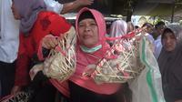 Salah seorang jemaah majelis tarbiyah, Wanaraja, Garut, Jawa Barat nampak tengah menerima pemberian 2 ekor ayam dalam perayaan 1 Muharram 1441 Hijriah di Garut (Liputan6.com/Jayadi Supriadin)