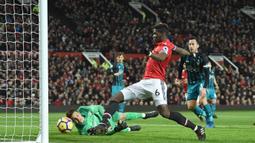 Aksi pemain Manchester United, Paul Pogba mencoba melewati adangan kiper Southampton pada lanjutan Premier League di Old Trafford, Manchester, (30/12/2017). MU hanya bermain imbang 0-0.  (AFP/Oli Scarff)