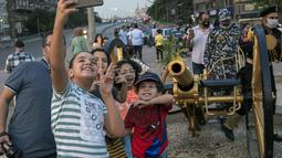 Warga berswafoto dekat sebuah meriam iftar di Giza, Mesir, Sabtu (16/5/2020). Meriam iftar ditembakkan setiap hari selama bulan suci Ramadan untuk menandakan waktu berbuka puasa (iftar) bagi umat muslim saat matahari terbenam. (Xinhua/Ahmed Gomaa)