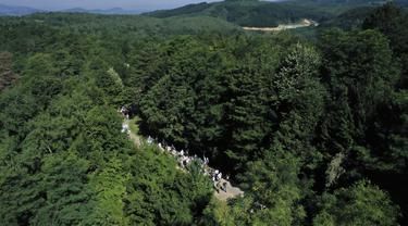 Rakyat Bosnia berjalan melalui daerah pegunungan dekat Crni Vrh saat memperingati 25 tahun pembantaian Srebrenica di Bosnia, Rabu (8/7/2020). Acara yang diikuti beberapa korban selamat dari pembantaian tersebut mengambil rute saat mereka melarikan diri dari pasukan Serbia. (AP Photo/Kemal Softic)