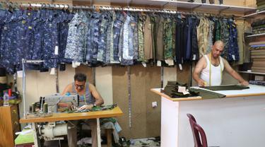 Penjahit Irak menyelesaikan pembuatan seragam militer di Baghdad (13/9). Perang yang berlangsung di Irak membuat para penjahit pakaian biasa kebanjiran orderan membuat seragam militer dan aksesorisnya. (AFP Photo/Sabah Arar)