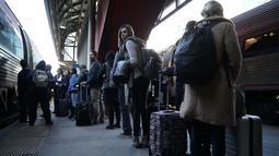 Penumpang antre untuk menaiki kereta Amtrak pada hari sebelum liburan Thanksgiving di Union Station, Washington, Rabu (21/11). Tradisi mudik di AS dilakukan saat Thanksgiving Day yang jatuh pada Kamis keempat bulan November. (Alex Wong/Getty Images/AFP)