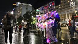 Pedagang menjual aksesoris rambut pada malam pergantian tahun di kawasan Bundaran HI, Jakarta, Senin (31/12). Pergantian tahun dimanfaatkan pedagang untuk mencari keuntungan dengan berjualan pernak pernik tahun baru.(Liputan6.com/Angga Yuniar)