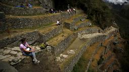 Wisatawan bersantai di tebing benteng Inca Machu Picchu, Peru, Rabu (12/8/2015). Machu Picchu sering juga disebut Kota Inca yang hilang yang terletak di wilayah pegunungan pada ketinggian sekitar 2.350 m di atas permukaan laut. (REUTERS/Pilar Olivares)