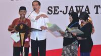 Jokowi menyerahkan sertifikat hak atas tanah program strategis nasional di Gedung New Sari Utama Convention Hall, Jember. (Biro