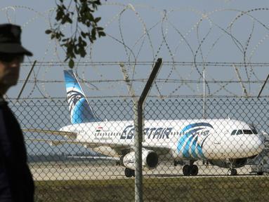 Seorang polisi berjaga di dekat pesawat milik maskapai Mesir, EgyptAir, yang dibajak dan dipaksa mendarat di Bandara Larnaca, Siprus, Selasa (29/3). Pembajak adalah seorang penumpang yang mengklaim membawa sabuk bahan peledak. (REUTERS/Yiannis Kourtoglou)