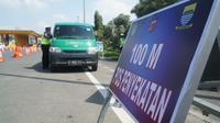 Petugas gabungan memeriksa kendaraan yang memasuki Kota Bandung dari Gerbang Tol Pasteur, Kota Bandung, Kamis (6/5/2021). Pemyekatan tersebut dilakukan selama larangan mudik lebaran 2021. (Liputan6.com/Huyogo Simbolon)
