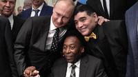 Legenda sepak bola, Diego Maradona dan Pele, foto bersama dengan Presiden Rusia, Vladimir Putin, saat menghadiri Drawing Piala Dunia 2018 di Kremlin Palace, Jumat (1/12/2017). Acara tersebut dihadiri legenda sepak bola dunia. (AFP/Alexey Nikolsky)