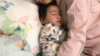 Salah satu pose tidur Nagita Slavina. Nagita nyenyak memeluk Rafathar. (Instagram @raffinagita1717)