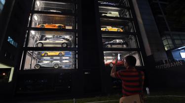 Seorang pria mengambil gambar vending machine atau mesin penjual otomatis berisi mobil-mobil mewah di gedung Autobahn Motors, Singapura, Kamis (18/5). Vending machine berbentuk bangunan bertingkat itu dapat menampung hingga 60 mobil. (ROSLAN RAHMAN/AFP)