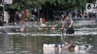Warga menuntun sepeda saat melintasi banjir yang merendam Jalan RA Kartini, Bekasi, Jawa Barat, Kamis (2/1/2020). Banjir yang merendam Jalan RA Kartini sejak kemarin melumpuhkan akses kendaraan dan perekonomian warga setempat. (merdeka.com/Iqbal Nugroho)